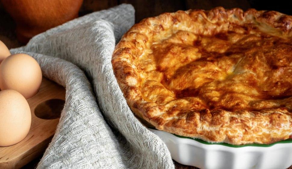 Torta rustica al formaggio sul tavolo con un panno e delle uova